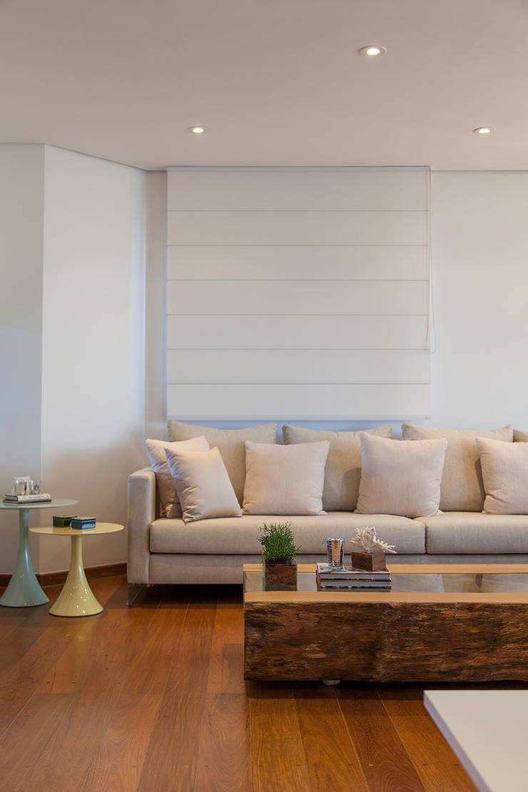Madeira em pauta para um casal que adora receber: Sala de estar  por Helô Marques Associados