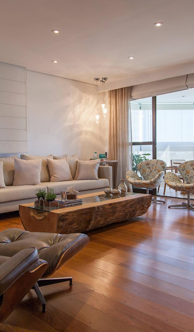 Madeira em pauta para um casal que adora receber: Salas de estar  por Helô Marques Associados