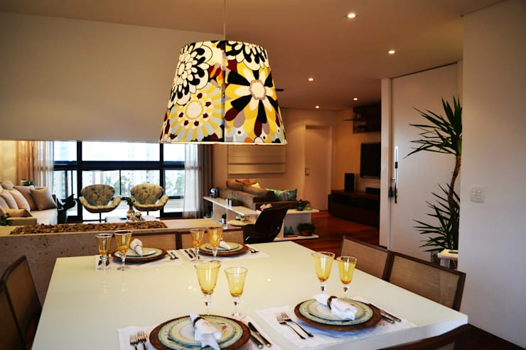 Madeira em pauta para um casal que adora receber: Sala de jantar  por Helô Marques Associados