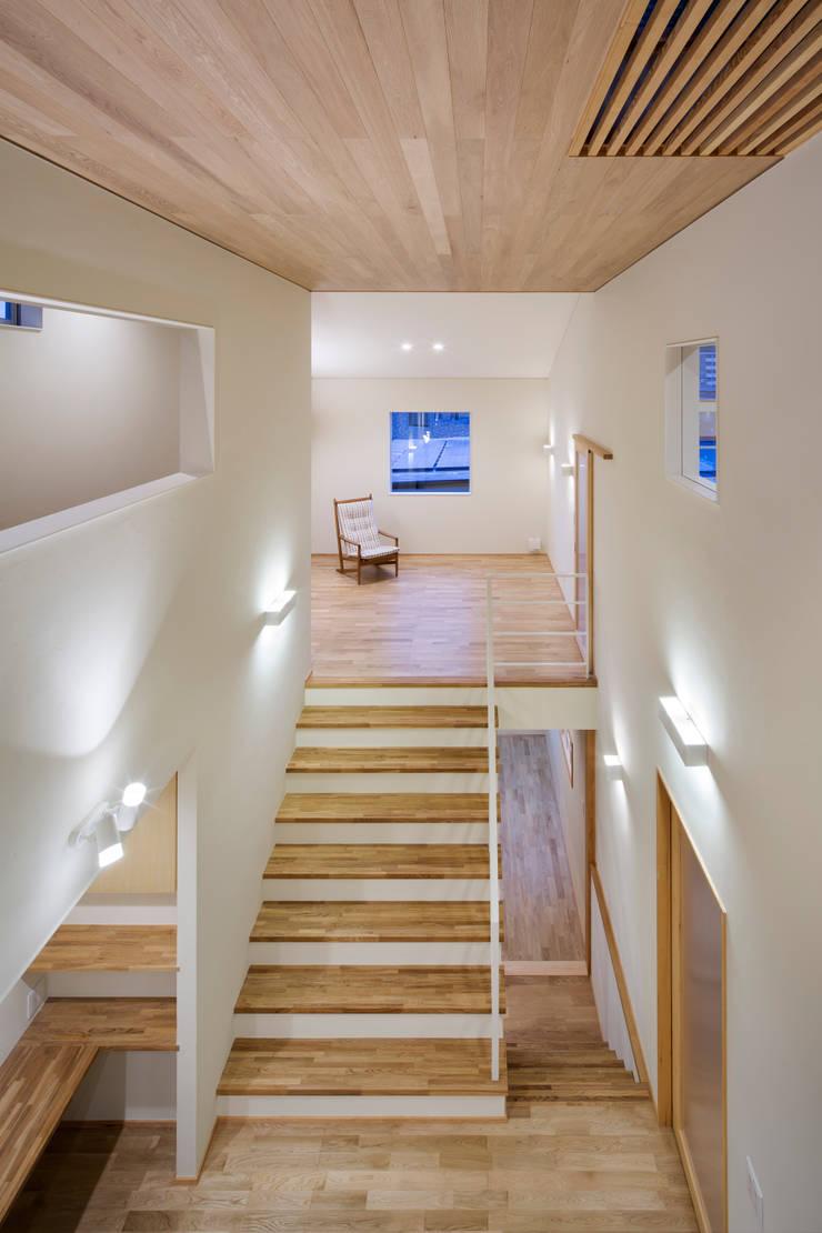家族をつなぐスキップフロアの家-吹抜け空間(夜)-: 小田達郎建築設計室が手掛けた廊下 & 玄関です。