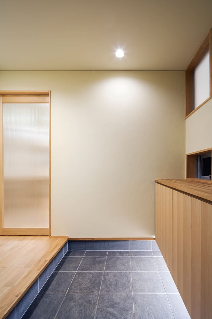 家族をつなぐスキップフロアの家-玄関-: 小田達郎建築設計室が手掛けた壁です。