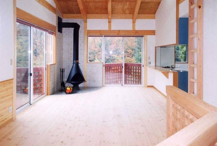 暖炉と書斎とせせらぎの聞こえる家: 建築設計事務所PRADOが手掛けたリビングです。