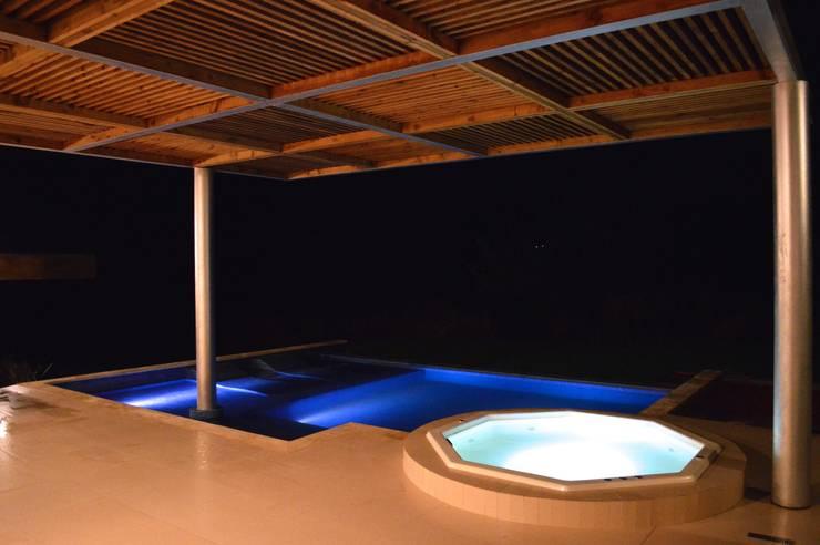 Tina de hidromasaje y piscina con iluminacion : Albercas de estilo  por Revah Arqs