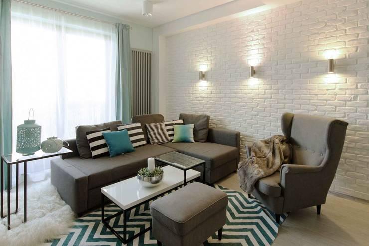 Mieszkanie z cegłą w tle: styl , w kategorii Salon zaprojektowany przez FAJNY PROJEKT