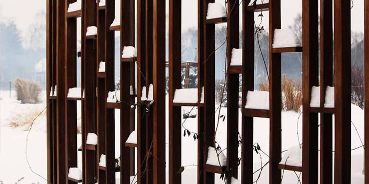 pergola pod pnącza z drewna egzotycznego nawet zimą jest ozdobna: styl , w kategorii  zaprojektowany przez Autorska Pracownia Architektury Krajobrazu Jardin ,