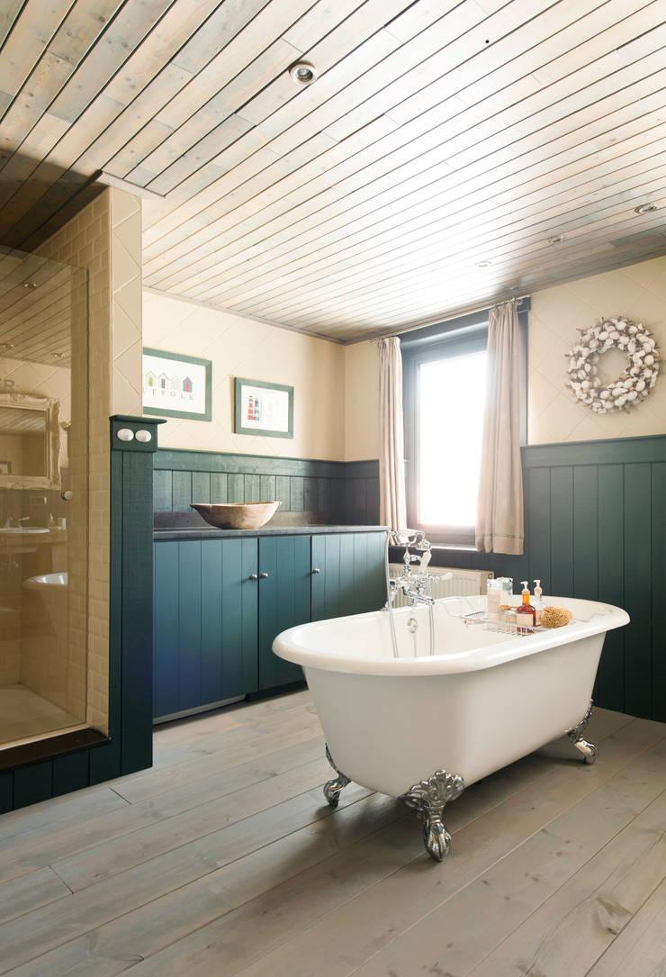 Het bad op pootjes het center van de landelijke badkamer:  Badkamer door Taps&Baths