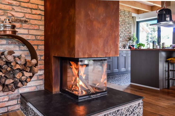 Kamin mit dreiseitiger Verglasung in Rostoptik, Wand aus alten Klinkersteinen:  Wohnzimmer von architektur. malsch - Planungsbüro für Neubau, Sanierung und Energieberatung