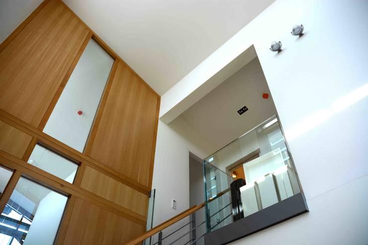 trappenhuis boven:  Gang en hal door TIEN+ architecten, Modern