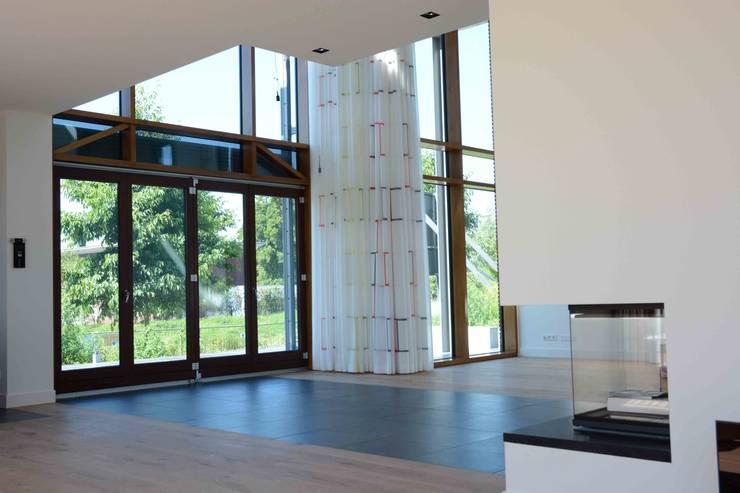 woonkamer met verschillende plafond hoogten:  Woonkamer door TIEN+ architecten, Modern
