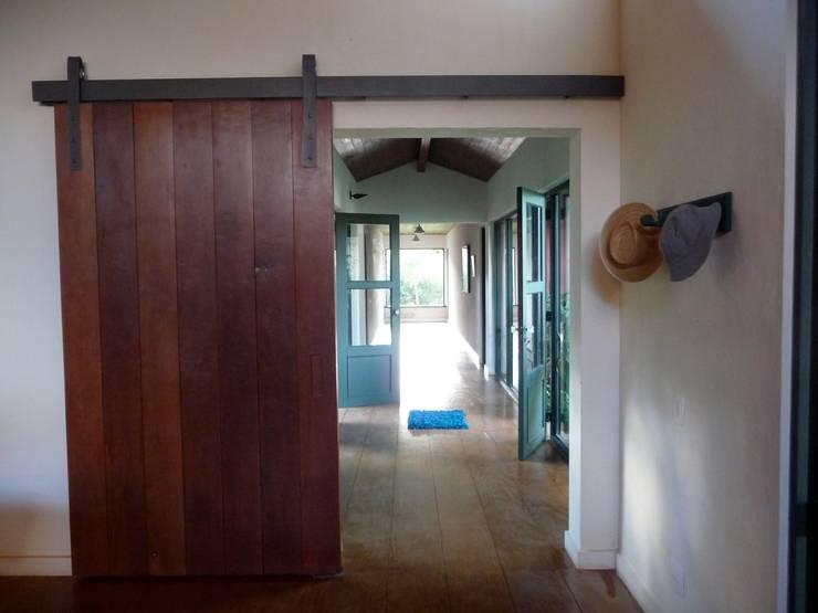 Hall de entrada e corredor para os quartos: Corredores e halls de entrada  por Ronald Ingber Arquitetura,Rústico