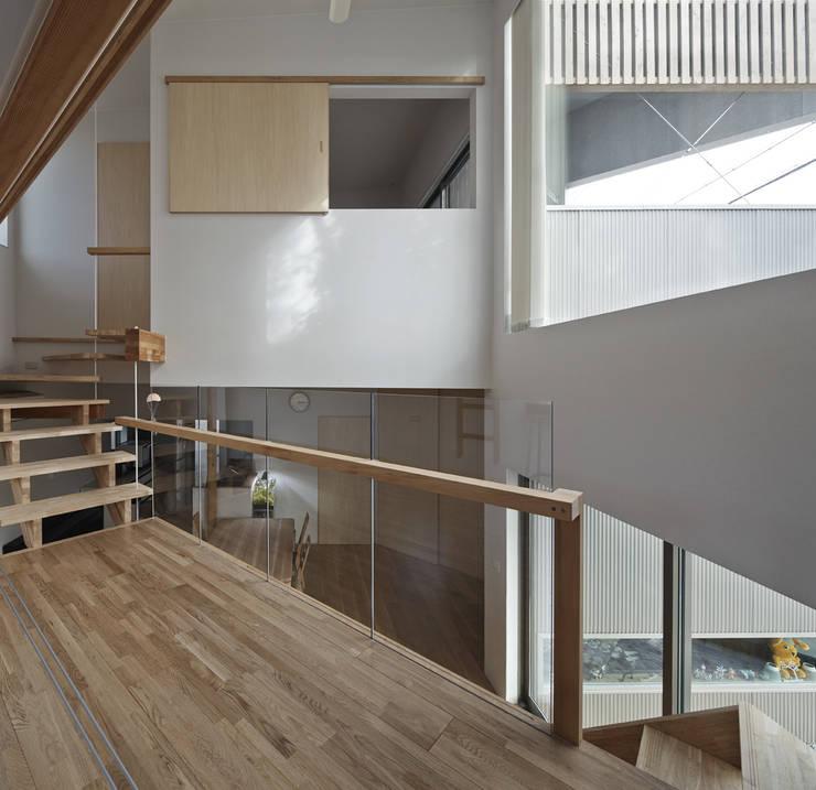 1.5階の廊下からダイニング方向を見る、正面上部の開口の奥は2階寝室: 宮武淳夫建築+アルファ設計が手掛けた廊下 & 玄関です。