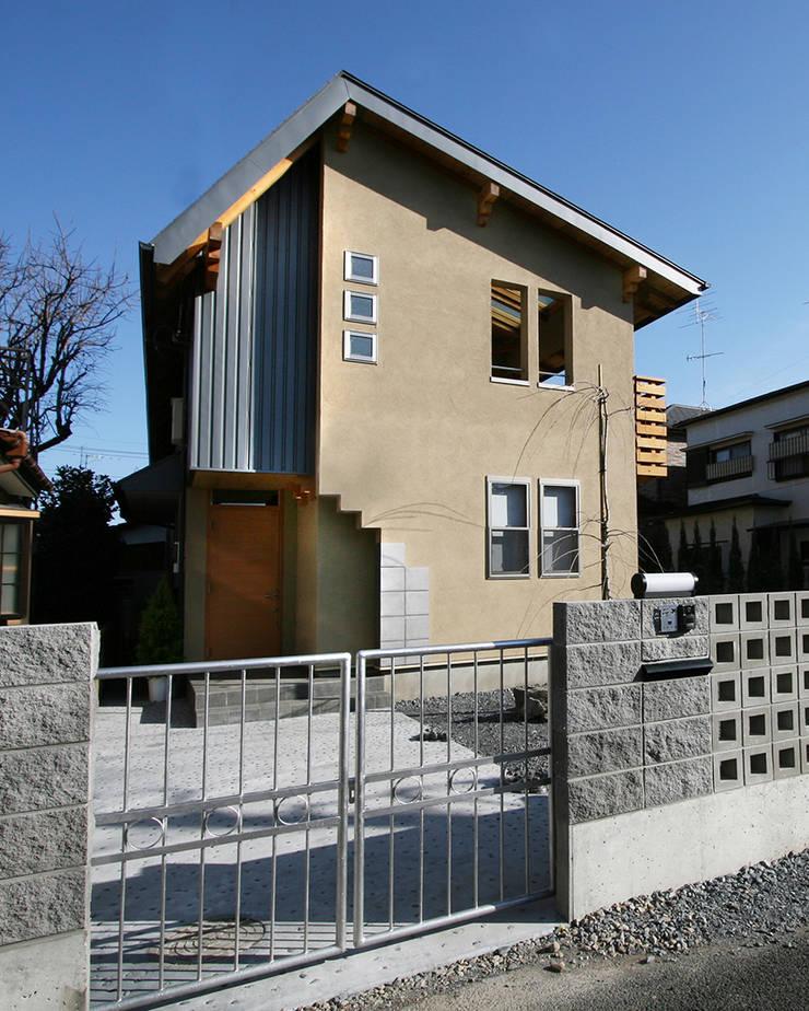 ゲートから西側ファサードを見る: 遠藤浩建築設計事務所 H,ENDOH  ARCHTECT  &  ASSOCIATESが手掛けた家です。,