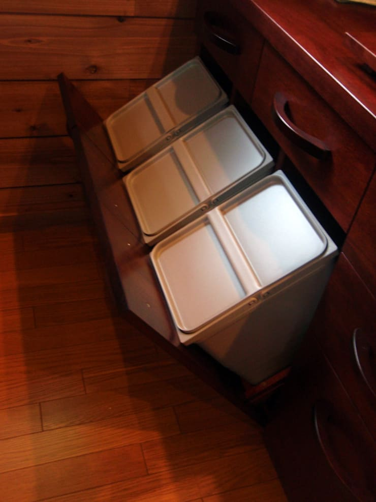 ゴミ箱を使い勝手良く隠す: 一枚板テーブルと無垢材家具・キッチンの祭り屋が手掛けたキッチンです。