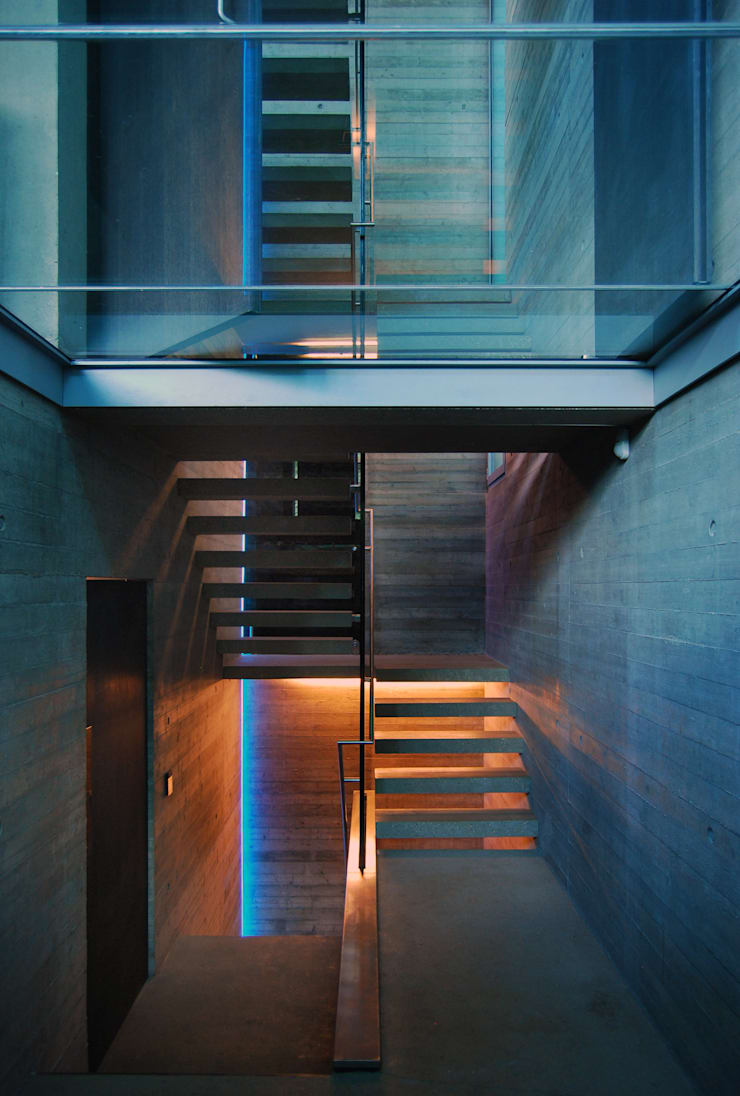 Cantilevered concrete staircase and glass floors:  Corridor & hallway by Eldridge London