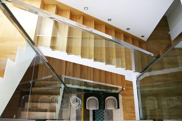 Vista picada de la escalera con dos cristaleras enfrentadas a modo de barandillas. La Pobla. Chiralt Arquitectos. : Pasillos y vestíbulos de estilo  de Chiralt Arquitectos