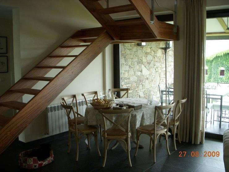 Vista del comedor y la escalera de madera  volada : Comedores de estilo clásico de DE DIEGO ZUAZO ARQUITECTOS