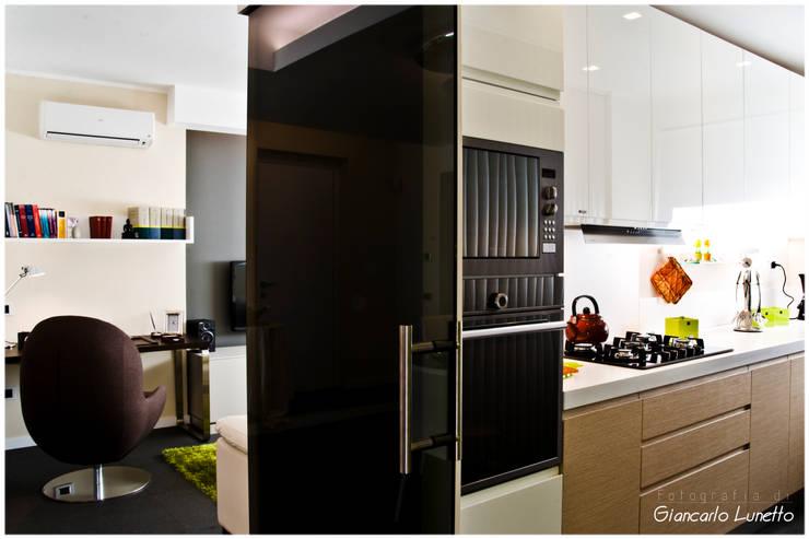Ingresso cucina dalla zona pranzo: Cucina in stile in stile Moderno di Ignazio Buscio Architetto