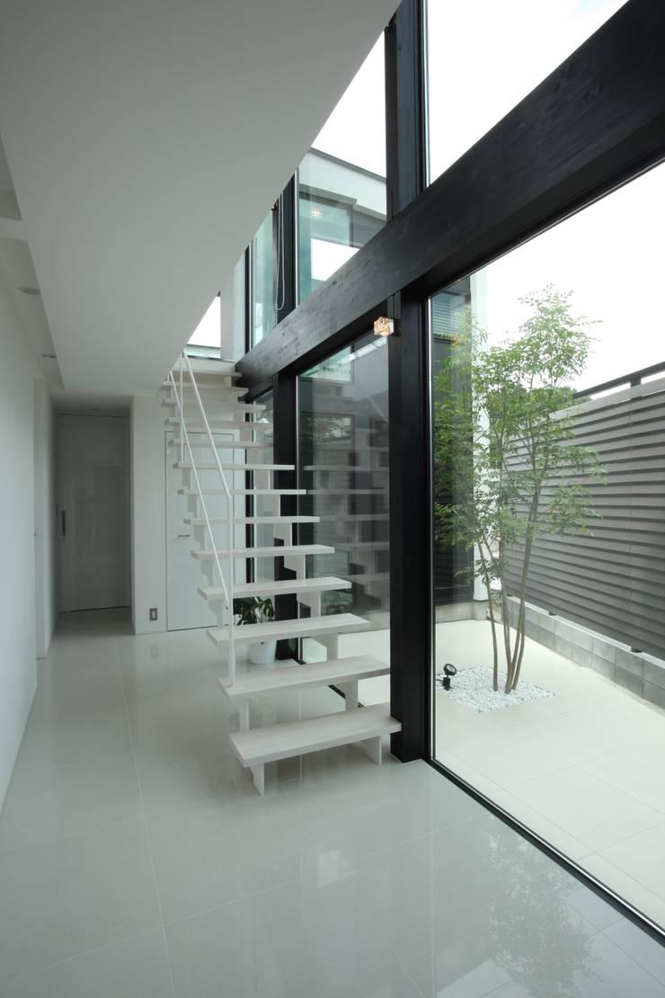 白い階段+ プライベートヤード: TERAJIMA ARCHITECTSが手掛けた廊下 & 玄関です。