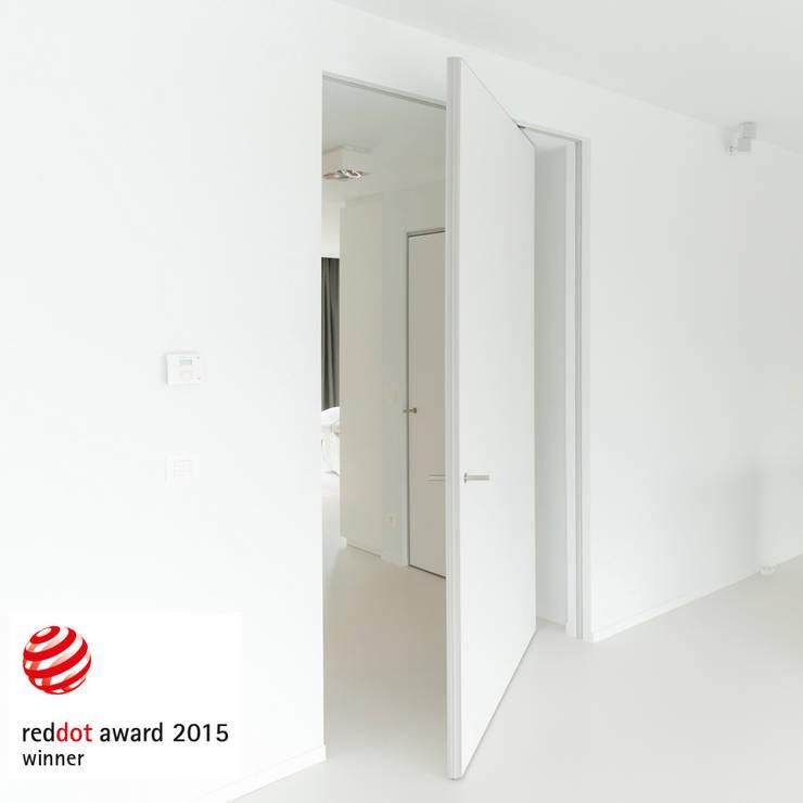 Moderne taatsdeur met een onzichtbaar kozijn:  Binnendeuren door Anyway Doors