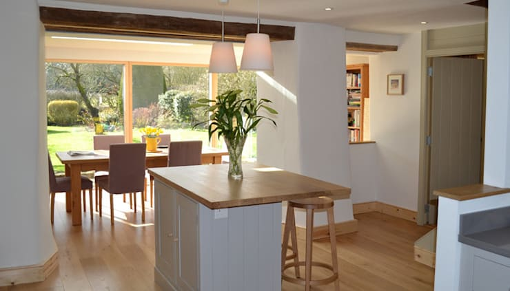 View from refurbished kitchen to garden room:  Kitchen by Hetreed Ross Architects