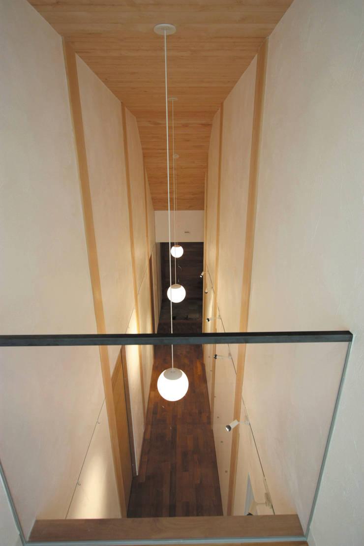 1階ギャラリー見下: 一級建築士事務所 ヒモトタクアトリエが手掛けた廊下 & 玄関です。