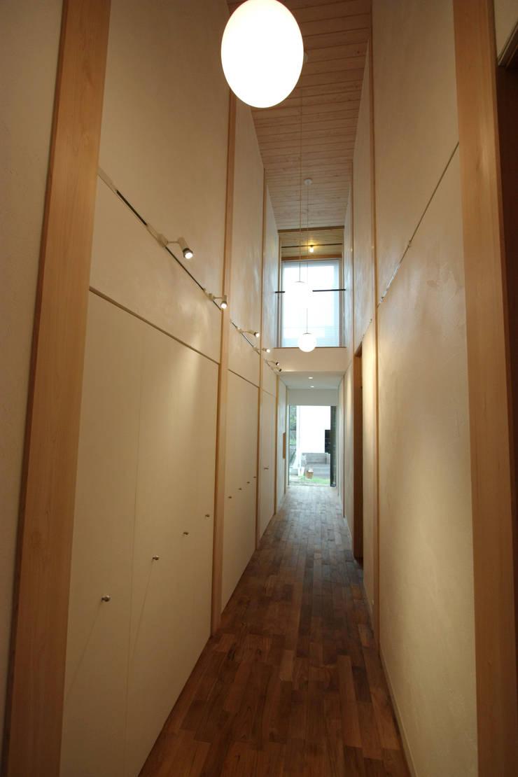 玄関から一直線に伸びるギャラリー: 一級建築士事務所 ヒモトタクアトリエが手掛けた廊下 & 玄関です。
