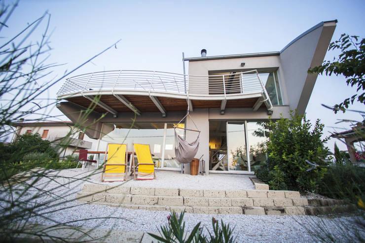 il doppio soggiorno e il giardino esterno: Case in stile  di RoccAtelier Associati
