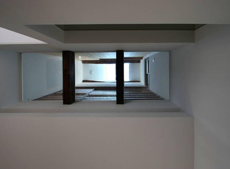 ガラス床を見上げる: 一級建築士事務所 ヒモトタクアトリエが手掛けた壁です。