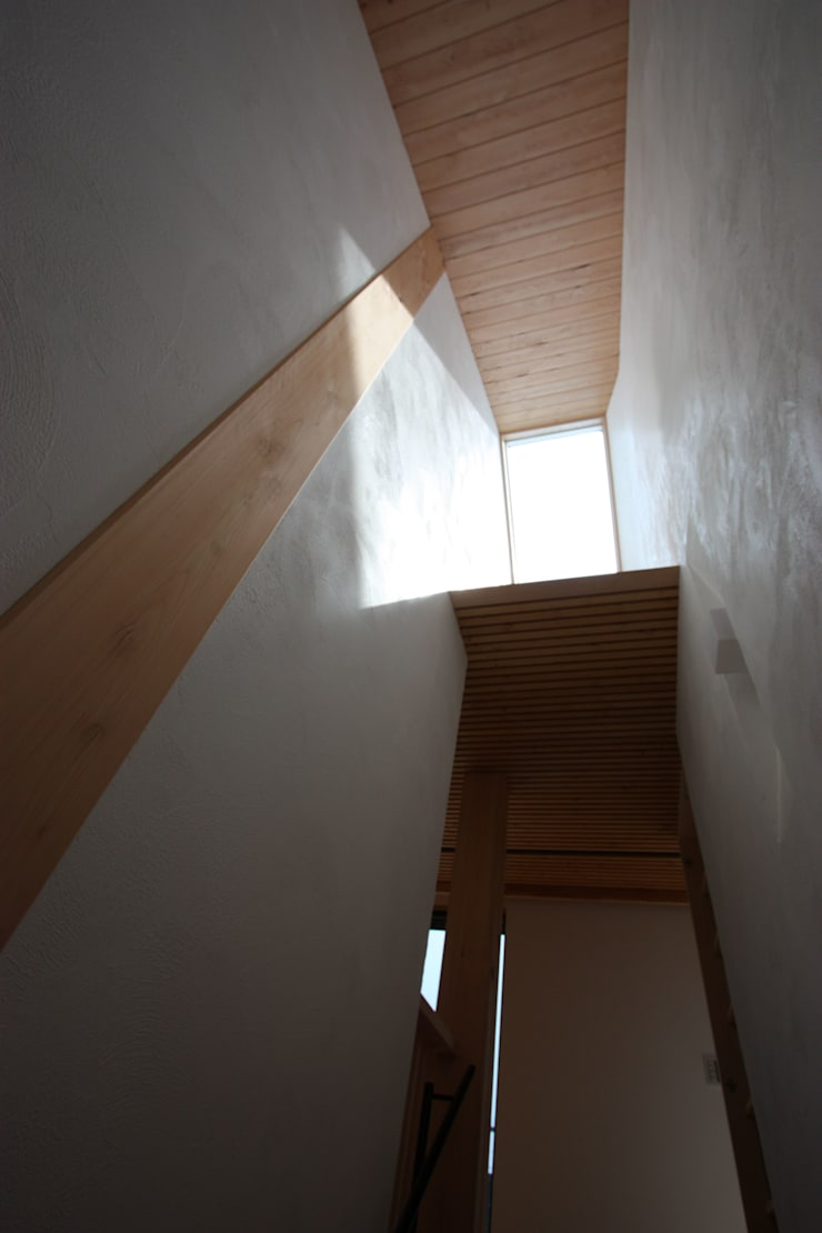 階段室見上げのトップライトと内部庇: 一級建築士事務所 ヒモトタクアトリエが手掛けた廊下 & 玄関です。