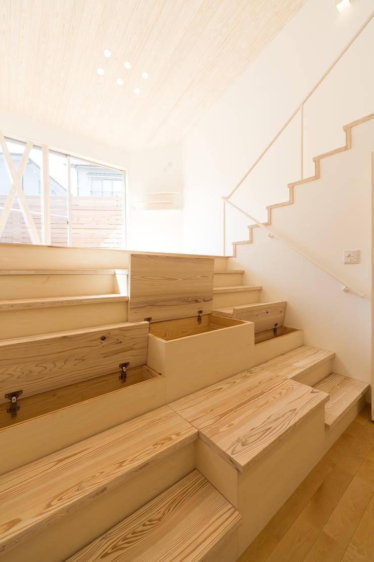 階段収納: 株式会社かんくう建築デザインが手掛けた廊下 & 玄関です。