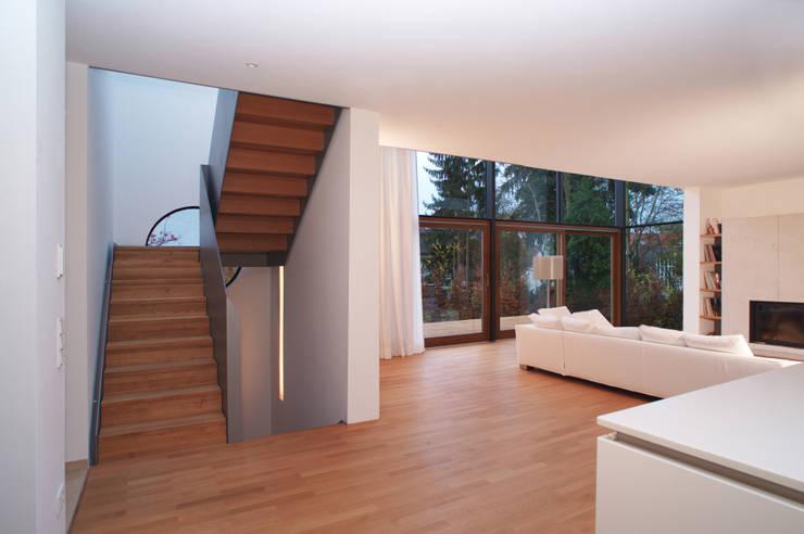 Wohnraum mit Aufgang zum Obergeschoß: moderne Wohnzimmer von Kramm + Strigl  Architekten und Stadtplaner