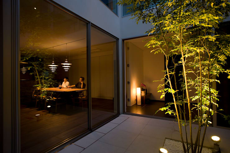 夕景:ライトアップされたテラスを楽しむ: TERAJIMA ARCHITECTSが手掛けた庭です。