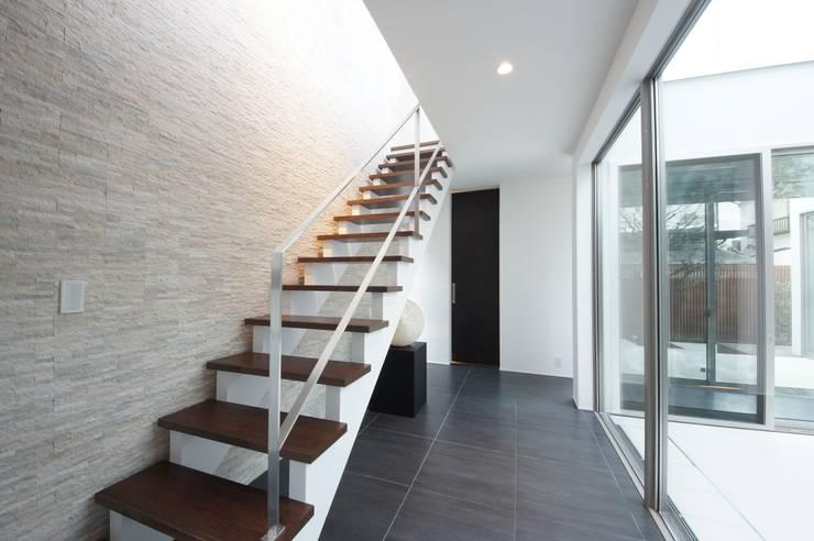灯りが表情を作りだす階段ホール: TERAJIMA ARCHITECTSが手掛けた廊下 & 玄関です。