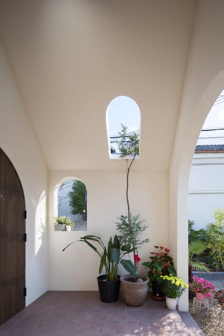エントランスポーチ: 株式会社 藤本高志建築設計事務所が手掛けた窓です。,モダン 木 木目調