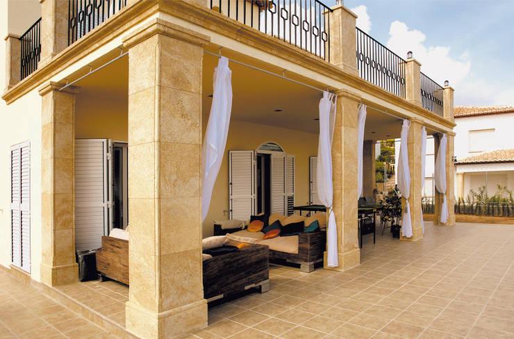 Porche con columnas de tosca: Balcones y terrazas de estilo  de Artosca