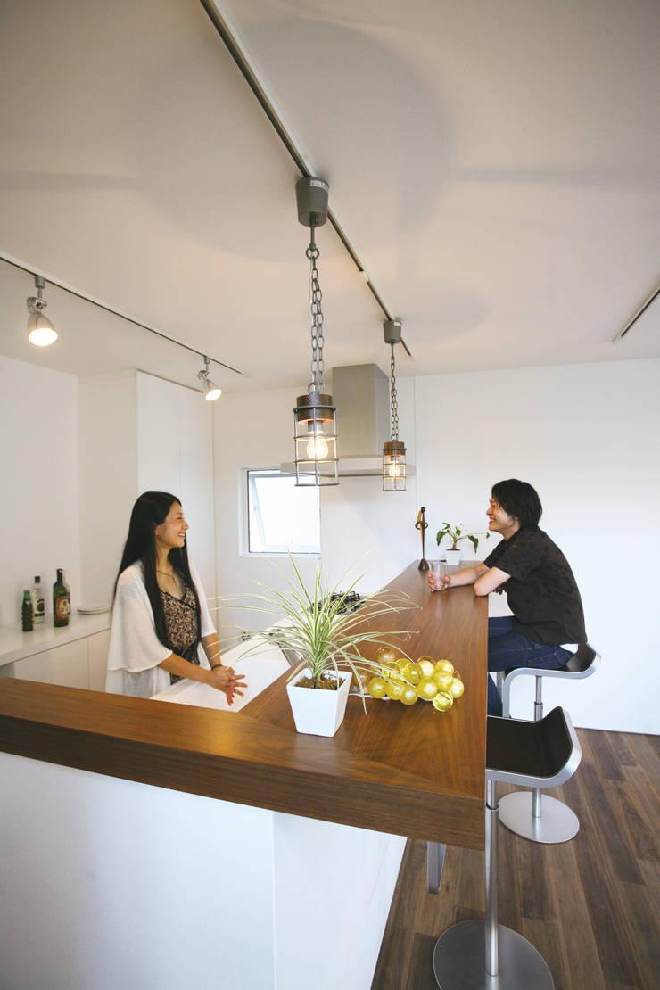 ウォルナットのカウンターにカフェテイストの照明: スターディ・スタイル一級建築士事務所が手掛けたキッチンです。
