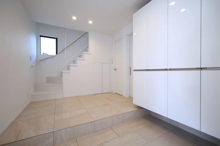 階段のデザインが印象的な玄関ホール: ナイトウタカシ建築設計事務所が手掛けた壁です。,