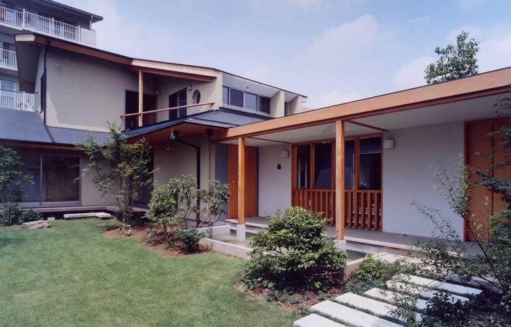 玄関と庭: 有限会社加々美明建築設計室が手掛けた家です。