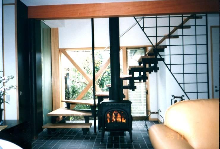 リビングの薪ストーブと階段: 有限会社加々美明建築設計室が手掛けたリビングです。