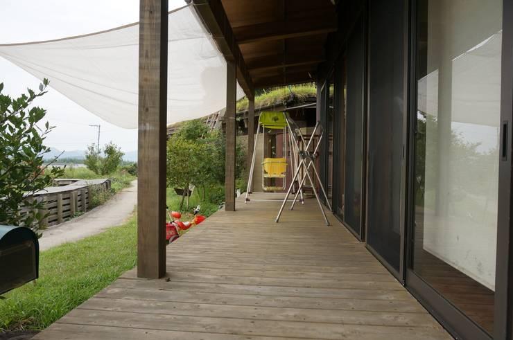 Ausgefallener Balkon, Veranda & Terrasse von 虎設計工房 Ausgefallen Massivholz Mehrfarbig