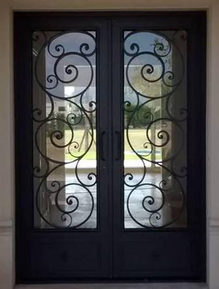 Puerta de hierro forjado: Ventanas y puertas de estilo  por Del Hierro Design