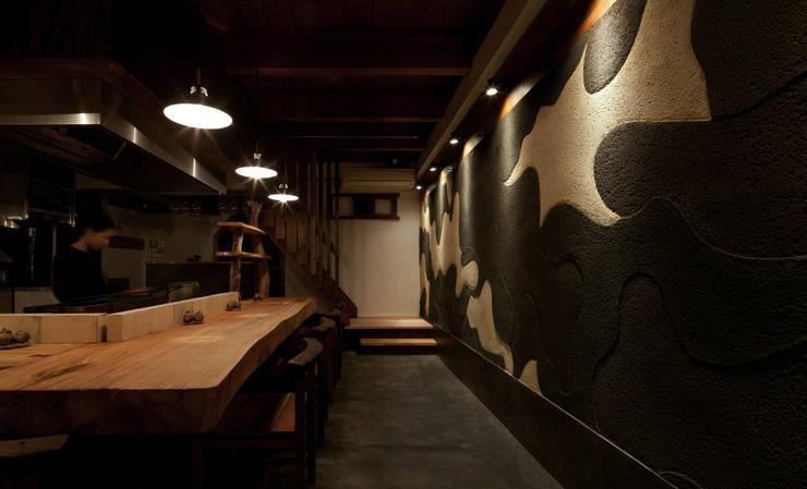 カウンター席: IZUE architect & associatesが手掛けた壁です。