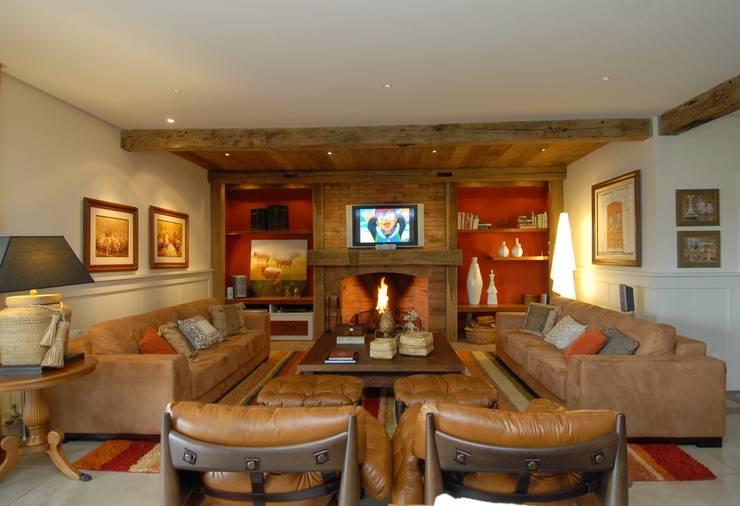Estar da lareira: Salas de estar  por Finkelstein Arquitetos