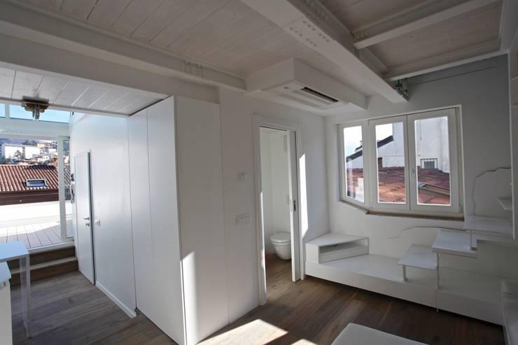 Ristrutturazione ed arredo su misura di un attico con soppalco: Ingresso & Corridoio in stile  di Mangodesign