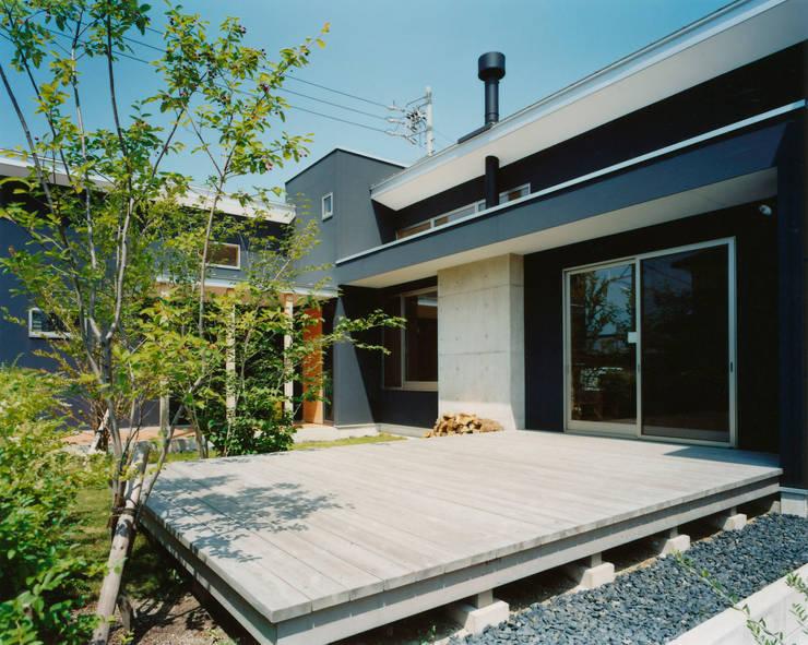 大きなウッドデッキがある中央の庭: アール・アンド・エス設計工房が手掛けた庭です。,