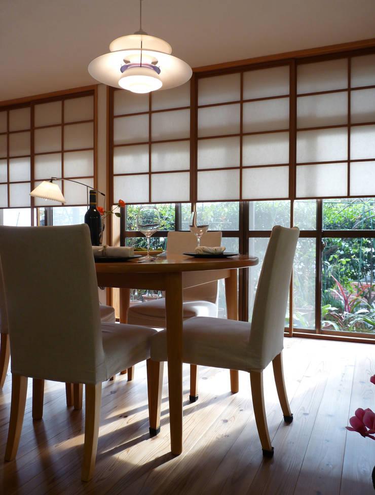 障子とバラの庭が居間に拡張性をあたえ広く見える: T設計室一級建築士事務所/tsekkeiが手掛けたリビングです。,モダン 木 木目調
