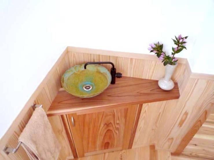 青銅色の手洗いと製作の木のカウンター: T設計室一級建築士事務所/tsekkeiが手掛けた浴室です。,モダン 木 木目調