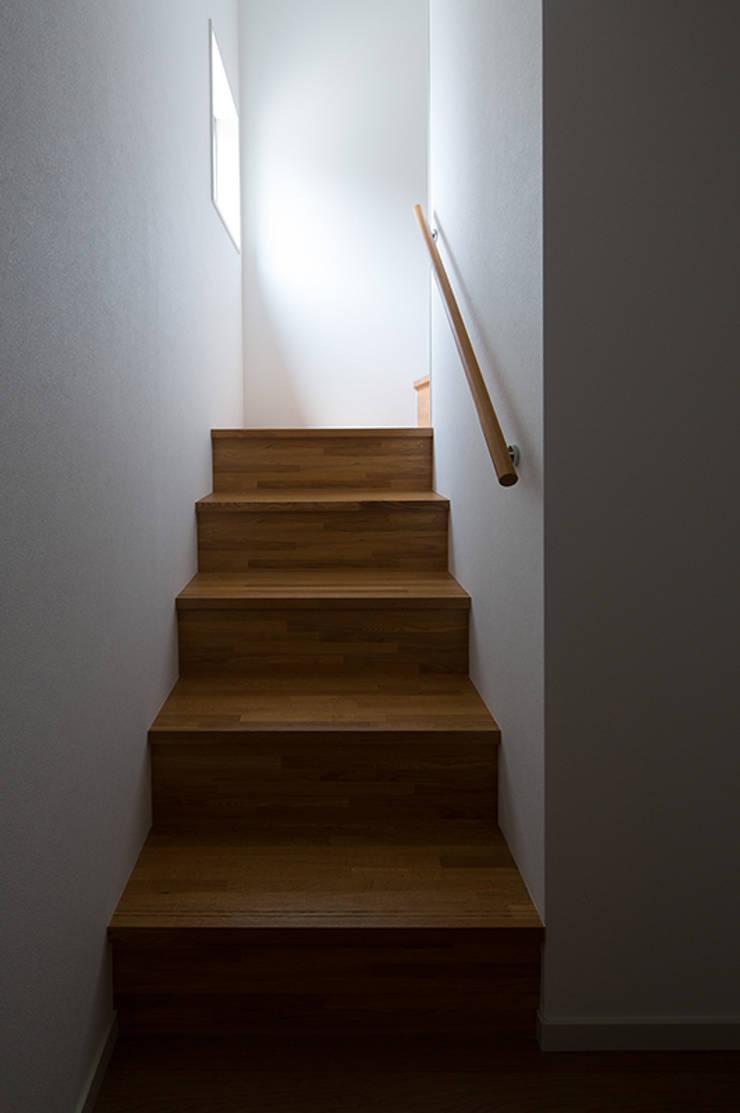 箕面桜井の二世帯住宅: ウメダタケヒロ建築設計事務所が手掛けた廊下 & 玄関です。