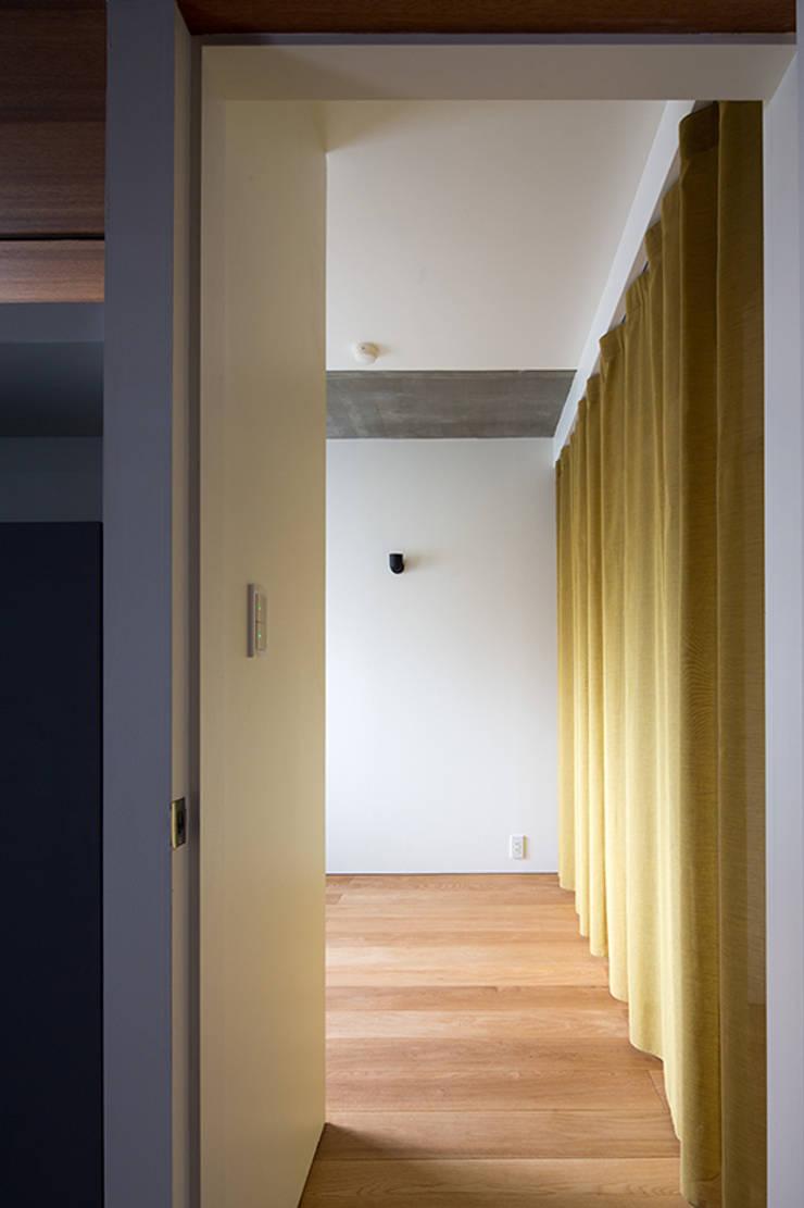 66㎡のフラットハウス(マンション住戸のスケルトン改修): ウメダタケヒロ建築設計事務所が手掛けた寝室です。,モダン