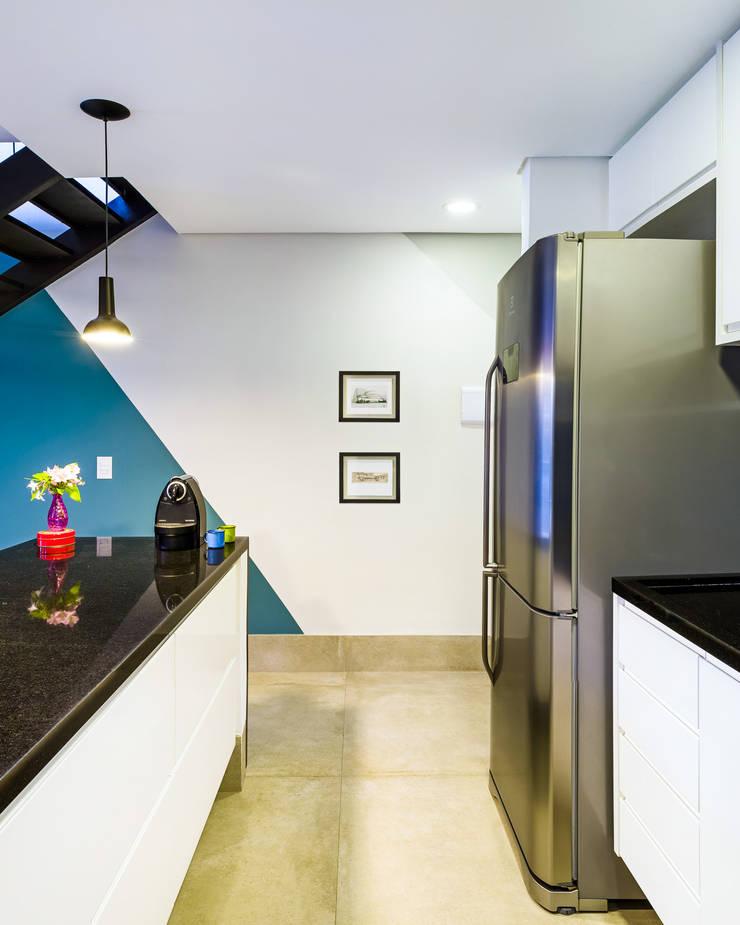 Cozinha branca e preta com destaque na pintura da parede: Cozinhas  por Studio ML,